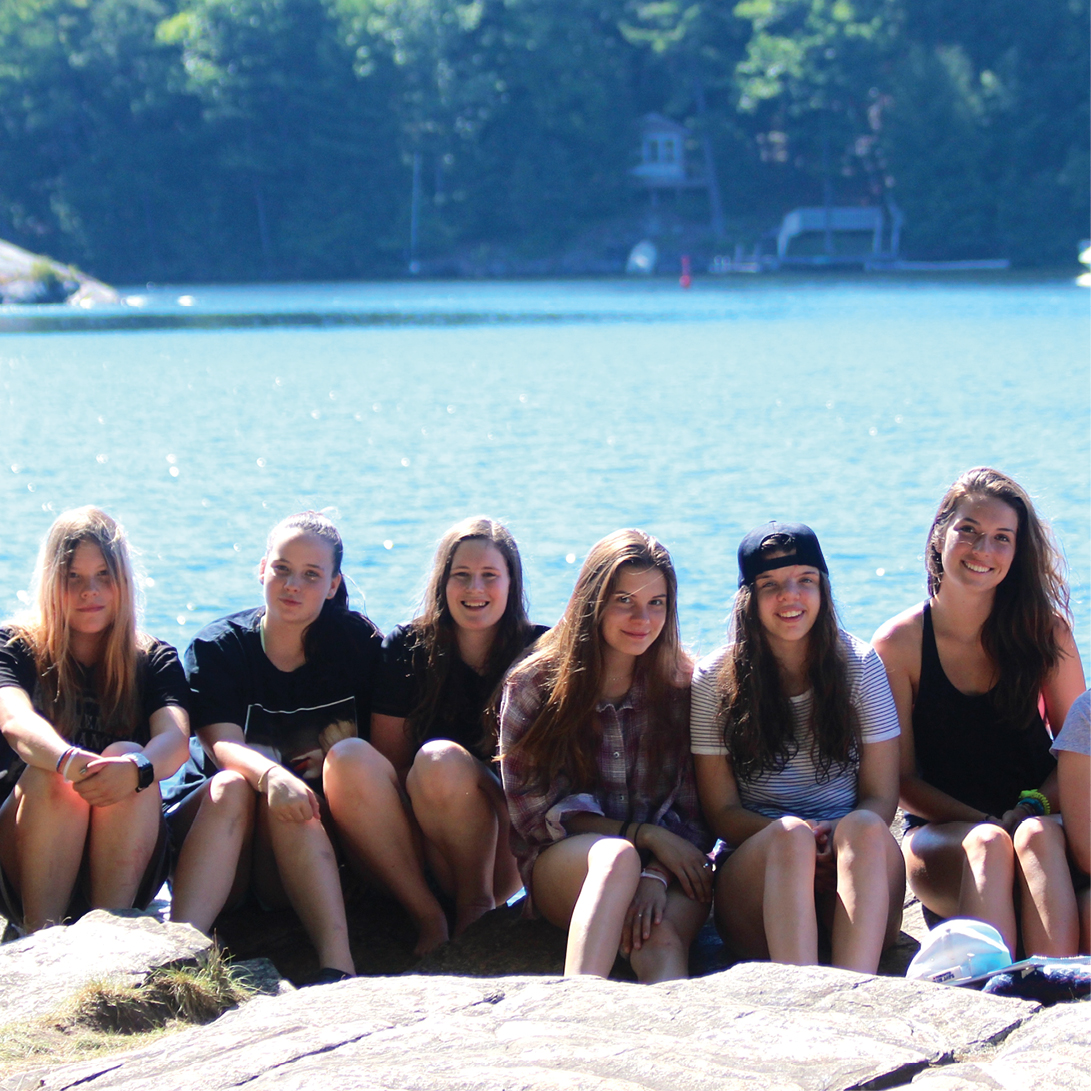 group of 6 girls on rock, lake in background