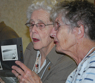 two elderly alumnae looking at photo album