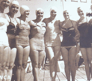 young women in swimsuits and bathing caps standing on dock, black and white photograph