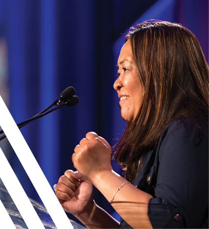 Passionate Filipino-Canadian woman standing with clenched fists speaking at podium with microphone