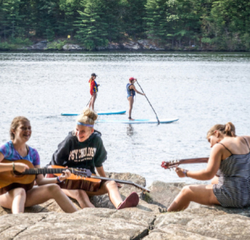 three girls playing guitars at camp